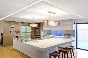 Interesting-Japanese-Modern-Kitchen-Design-with-White-Furniture-Brown-Wooden-Stools-and-Large-Island-on-Wooden-Floor